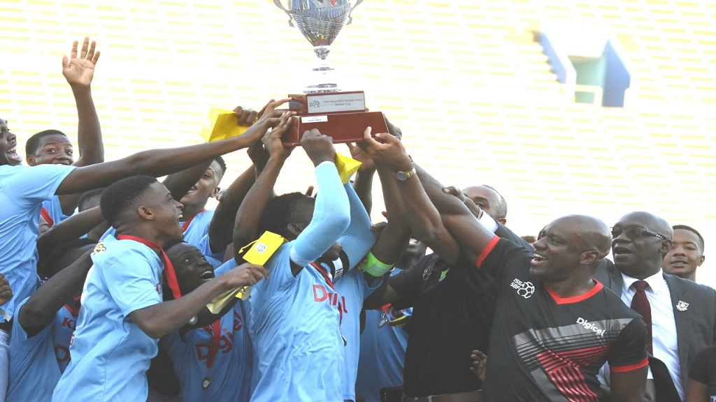 St Catherine High players celebrate after defeating Excelsior High 3-2 in the final of the 2019 ISSA/Digicel Walker Cup knockout competition at the National Stadium on Friday, November 29. At right is Elon Parkinson, public relations and communications manager of Digicel Jamaica. (PHOTO: Marlon Reid).