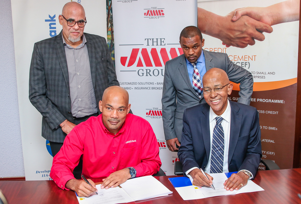 JMMB Bank Chief Executive Officer Jerome Smalling (seated, left) and Development Bank of Jamaica (DBJ) Managing Director Milverton Reynolds (seated, right) sign an agreement between the two parties at DBJ's offices on Monday, November 18, 2019, for JMMB Bank to offer the DBJ's redesigned Credit Enhancement Facility as JMMB Group CEO Keith Duncan (standing, left) and JMMB Country SME Specialist Kevin Foreman (standing, right) looks on.