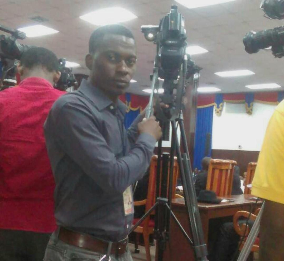 Ellecy Dieulassaint, cameraman de Télé Metropole, debout derrière sa caméra. Photo archives.