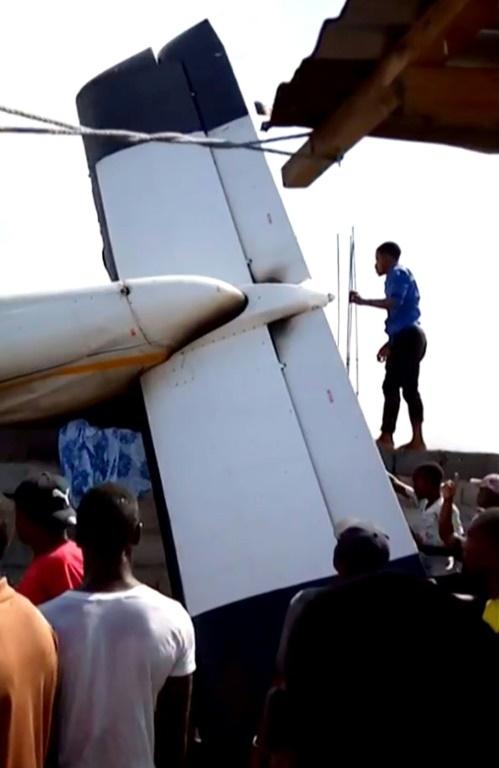 Des habitants de Goma, dans l'est de la RDC, s'affairent autour de l'épave d'un petit avion qui s'est écrasé sur des maisons le 24 novembre 2019, faisant 23 morts selon les secours