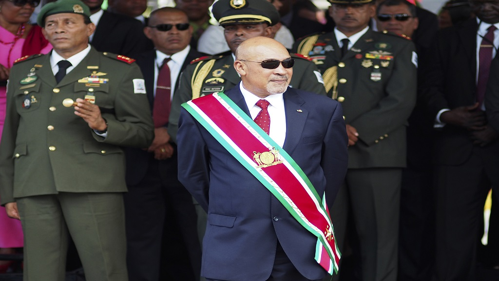 "In this Aug. 12, 2015 file photo, Suriname President Desire ""Desi"" Delano Bouterse observes a military parade, after being sworn in for his second term, in Paramaribo, Suriname. (AP Photo/Ertugrul Kilic, File)"