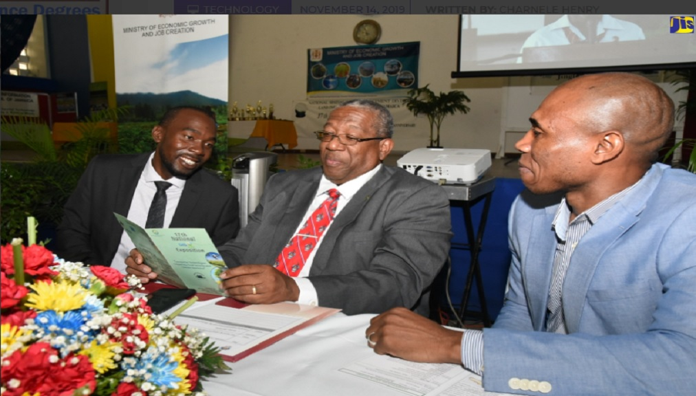 Principal of the University of West Indies (UWI) Mona Campus, Professor Dale Webber (centre), peruses a listing of the scheduled events for the 17th National GIS Day Exposition at the UWI, during the opening ceremony on Wednesday (November 13). Looking on (from left) are Principal Director for the National Spatial Data Management Division (NSDMD) in the Ministry of Economic Growth and Job Creation, Yaneke Watson; and lecturer at the College of Agriculture, Science and Education, Delford Morgan.
