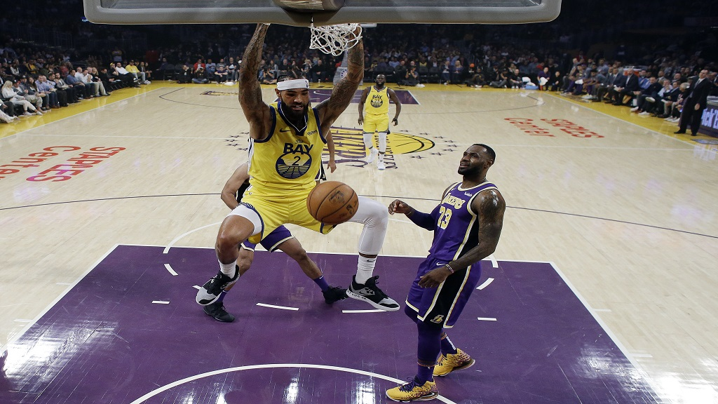 Golden State Warriors' Willie Cauley-Stein (2) dunks past Los Angeles Lakers' LeBron James (23) during the first half of an NBA basketball game Wednesday, Nov. 13, 2019, in Los Angeles. (AP Photo/Marcio Jose Sanchez).