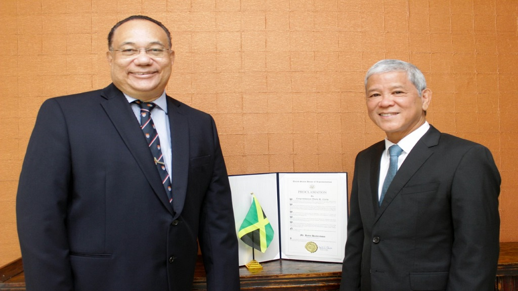 Ambassador Richard Bernal, pro-vice chancellor, global affairs of The University of The West Indies (left) presents noted Jamaican hotelier, Kevin Hendrickson, with a proclamation in his honor from the US House of Representatives.
