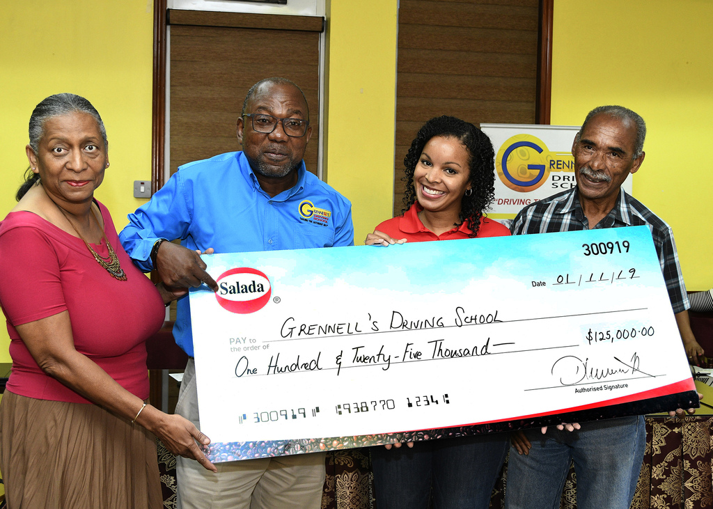 Salada Foods Jamaica business manager Sherianne Thompson Hart (second right), presents a sponsorship cheque valued at $125,000 to Alphonso Grennell (second left), managing director of Grennell's Driving School for the ninth staging of the Grennell's Road Safety 5K. Sharing in the moment are Claudia and Errol Alliman, parents of crash victim, Jason Alliman for whom the race is being held in memory.