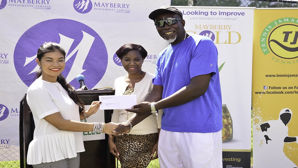 Stephanie Harrison (left), Digital Marketing Manager, Mayberry Investments Limited hands over a cheque to tennis pro Llockett Mcgregor during the launch of the junior tennis championship on Wednesday, November 13 at Liguanea Club.
