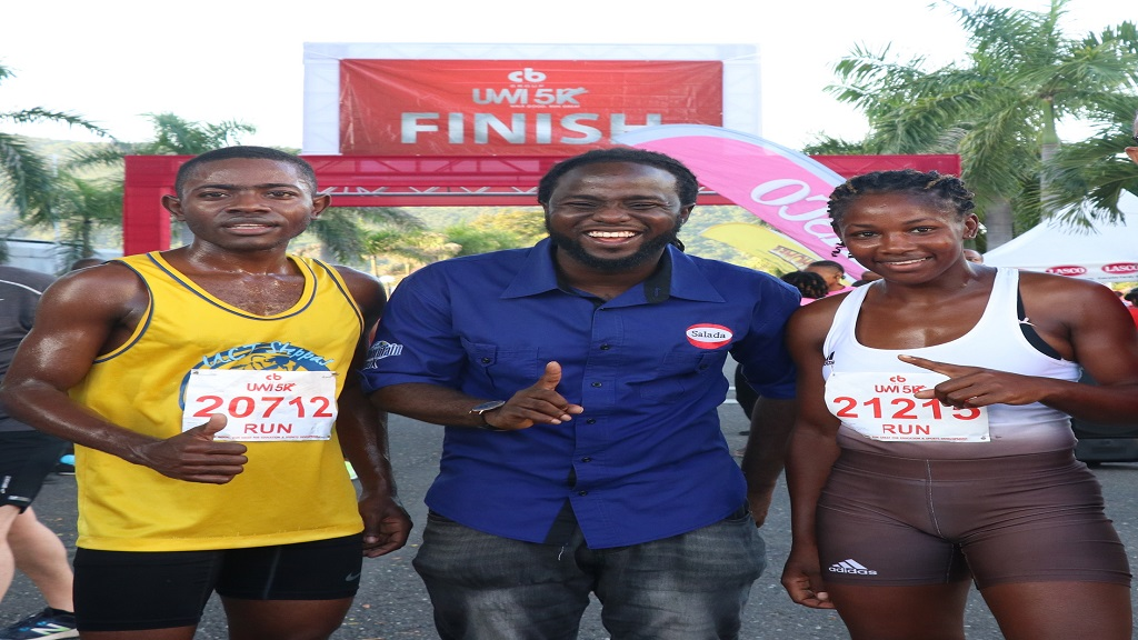 Marvin Kerr (centre), marketing coordinator at Salada Foods Jamaica congratulates first place finishers in the 5K run Henry Thomas of UCT Steppas (left) and Shanice Gordon of GC Foster College at the 2019 staging of the CB UWI 5K on Sunday, November 10, 2019 at the UWI Mona Campus.