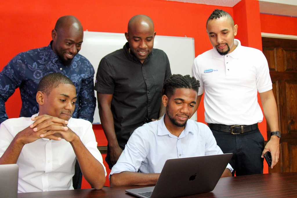 Directors Neil Lawrence (right) and Ryan Reid look on as Brainboxx's CEO Che-Andre Gordon (seated right) and COO Andrew Pettigrew share a presentation with Chairman Garth Walker.