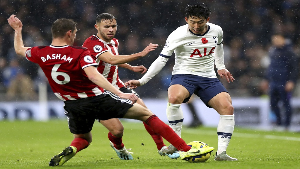 Tottenham's Son Heung-min, right, battles for the ball with Sheffield United's George Baldock, centre and Chris Basham during the English Premier League football match at Tottenham Hotspur Stadium, in London, Saturday, Nov. 9, 2019. (Bradley Collyer/PA via AP).