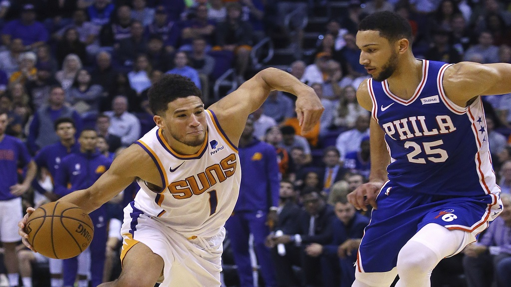 Phoenix Suns guard Devin Booker (1) drives past Philadelphia 76ers guard Ben Simmons (25) during the second half of an NBA basketball game, Monday, Nov. 4, 2019, in Phoenix. (AP Photo/Ross D. Franklin).