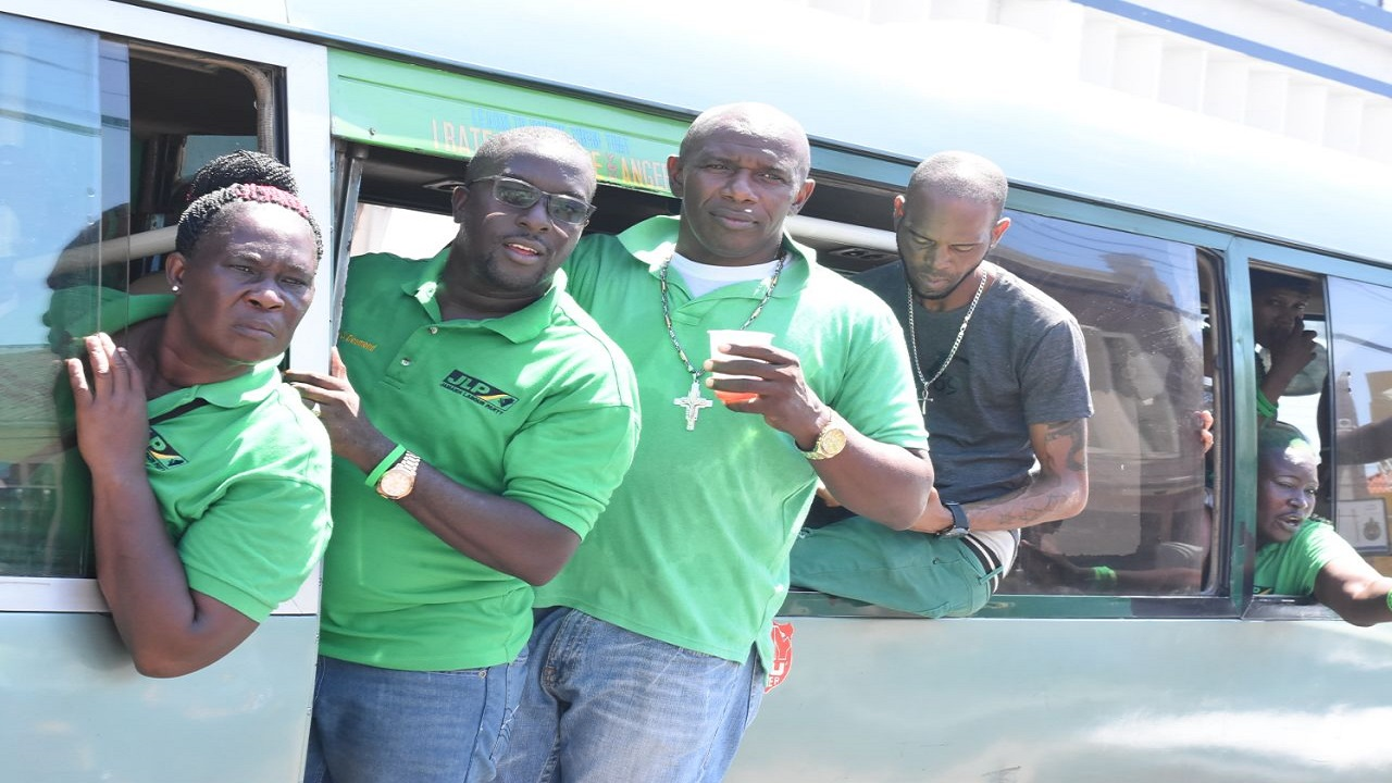 File photo of Labourites traveling on a bus. Ahead of the JLP conference on Sunday, the police have warned drivers not to allow passengers to hang from the doors of motor buses among other violations.