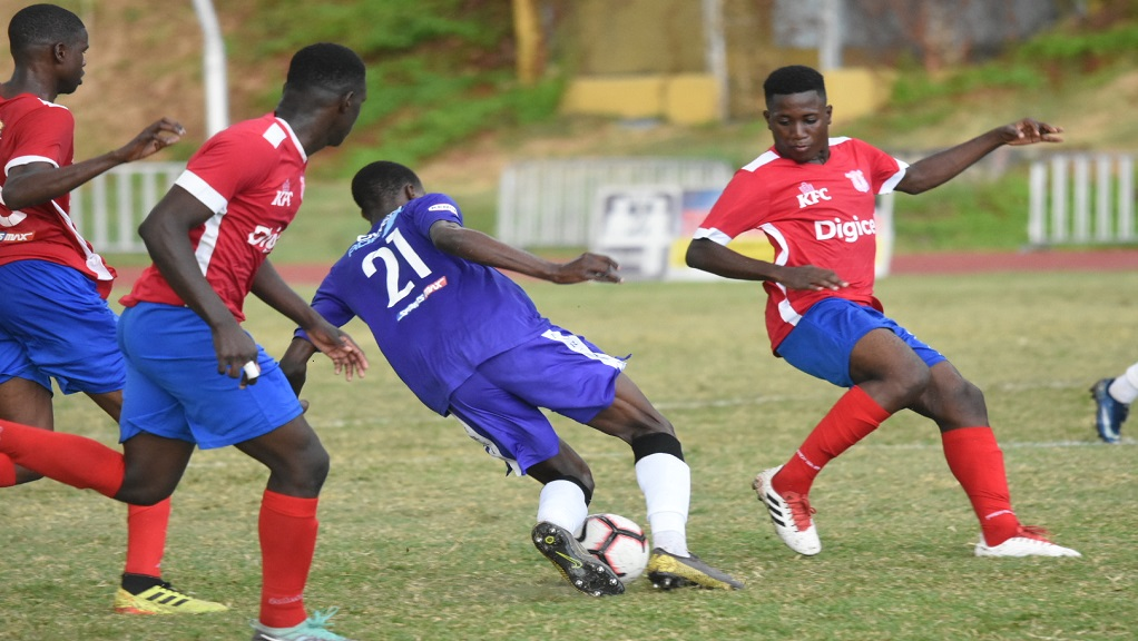 Tyreese Williams of Kingston College (KC) takes on three Camperdown High players during their final Group G quarter-final round game of the ISSA/Digicel Manning Cup football competition at the Stadium East field on Tuesday, November 12, 2019. (PHOTOS: Marlon Reid).