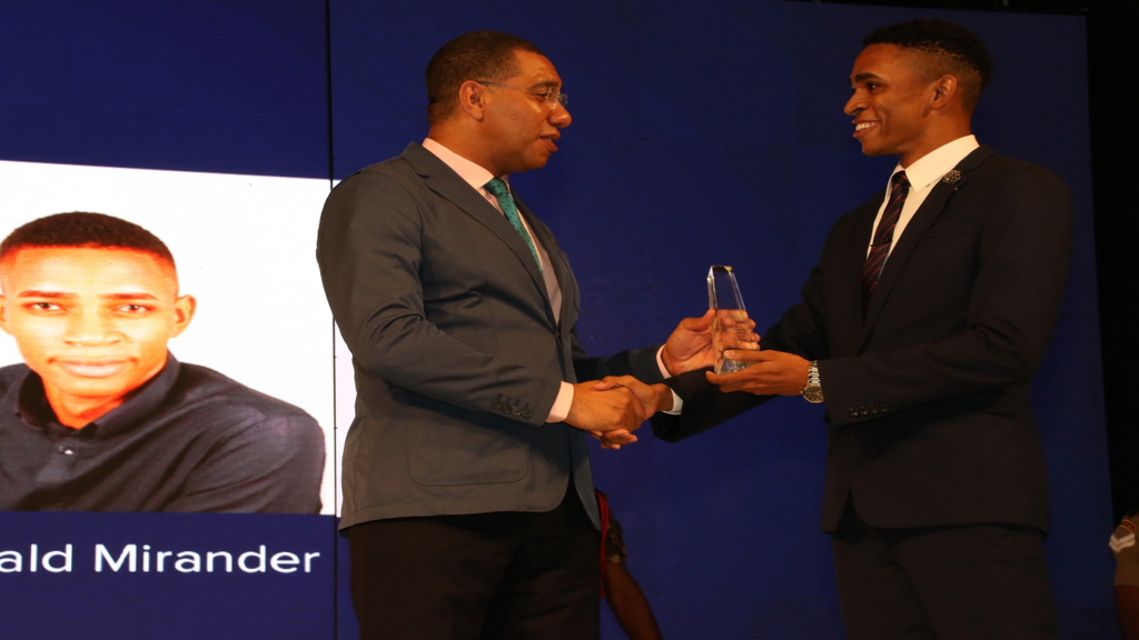 Prime Minister Andrew Holness presents a recipient of the Prime Minister's National Youth Awards for Excellence at the 2018 staging of the awards ceremony.