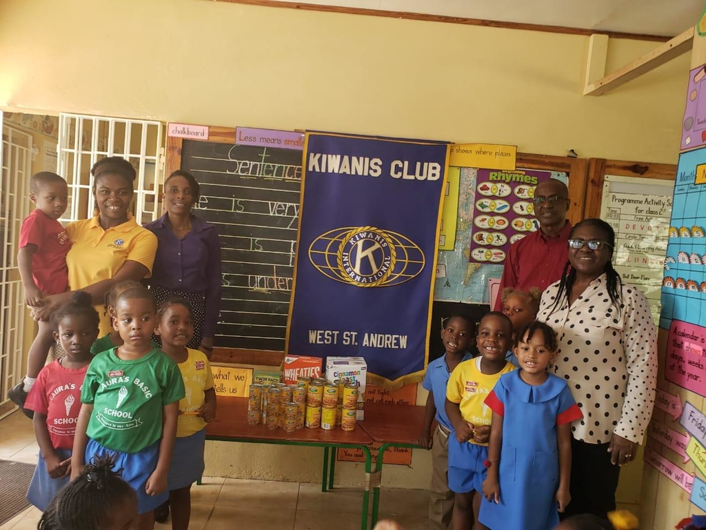 From left: KCWSA Public Relations Chairman Marshalyn Rose, KCWSA President Marie Brown, Distinguished President James McNish and Laura's Basic School Principal Edith Chaplin stand with the children beside the donated items to the school on Friday.