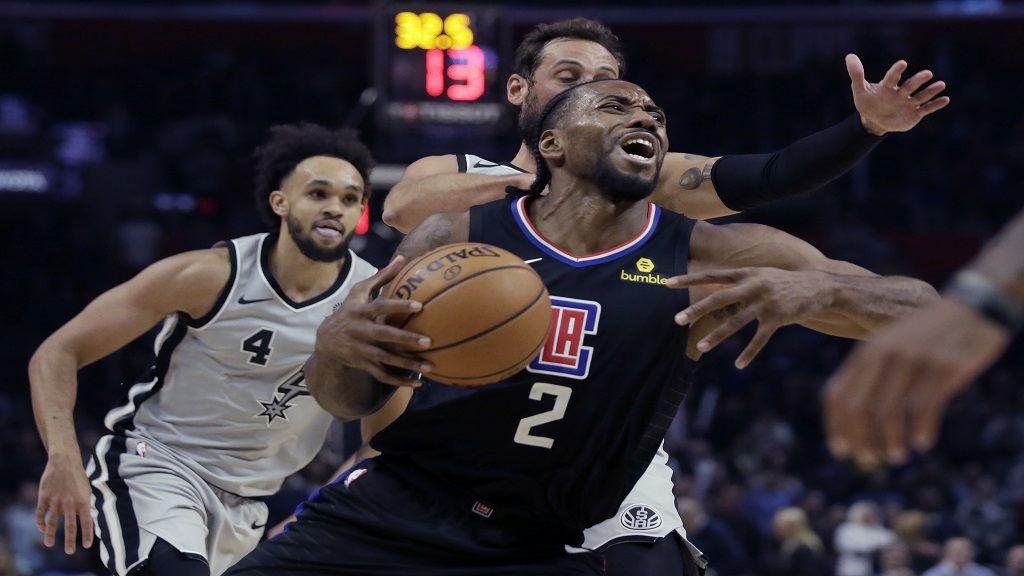 Los Angeles Clippers forward Kawhi Leonard drives to the basket past San Antonio Spurs guard Marco Belinelli, behind, of Italy, and guard Derrick White, left, during the second half of an NBA basketball game in Los Angeles, Thursday, Oct. 31, 2019. (AP Photo/Alex Gallardo).