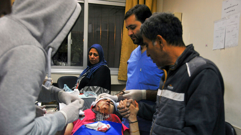 In this photo released by the Syrian official news agency SANA, a paramedic treats an injured woman wounded by Israeli missile strikes at a hospital in Damascus, Syria, November 20, 2019. (SANA via AP)