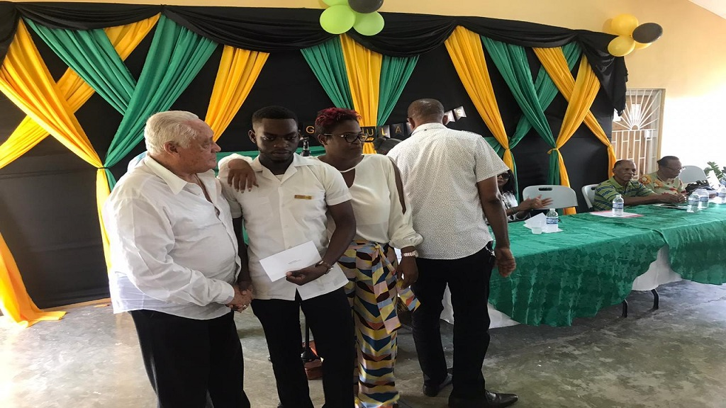 Central Clarendon Member of Parliament (MP), Mike Henry (left), presents an education grant to final-year medical student at the University of the West Indies (UWI), Kenyata Thomas, at a ceremony at West Park Community Centre in May Pen, Clarendon last Sunday.