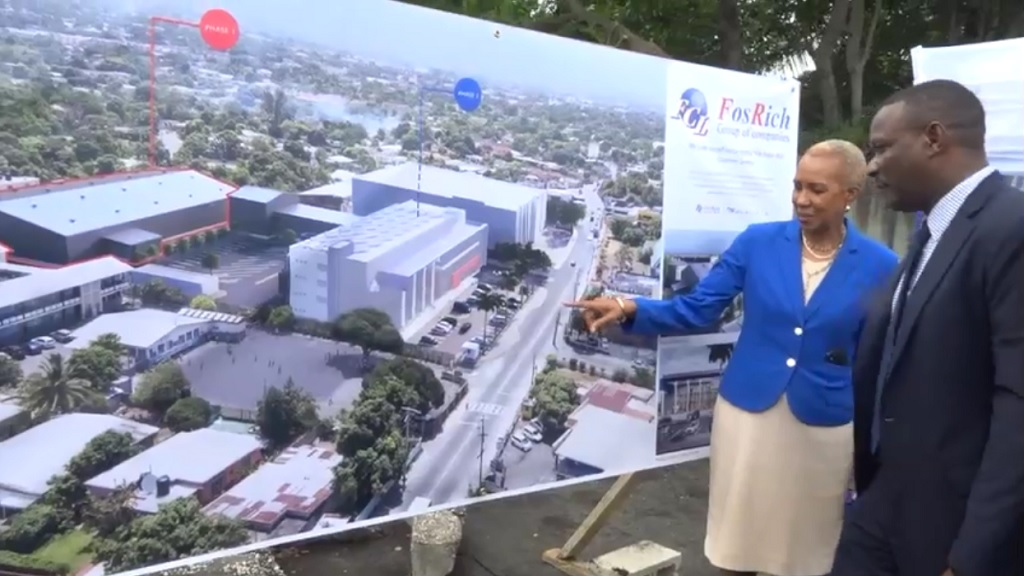 Energy Minister Fayval Williams examines an artist's impression of the multi-million dollar FosRich warehouse at a ground-breaking for the facility. With Williams, is FosRich Managing Director Cecil Foster.
