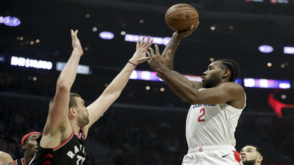 Los Angeles Clippers forward Kawhi Leonard, right, shoots over Toronto Raptors center Marc Gasol during the second half of an NBA basketball game in Los Angeles, Monday, Nov. 11, 2019. (AP Photo/Chris Carlson).