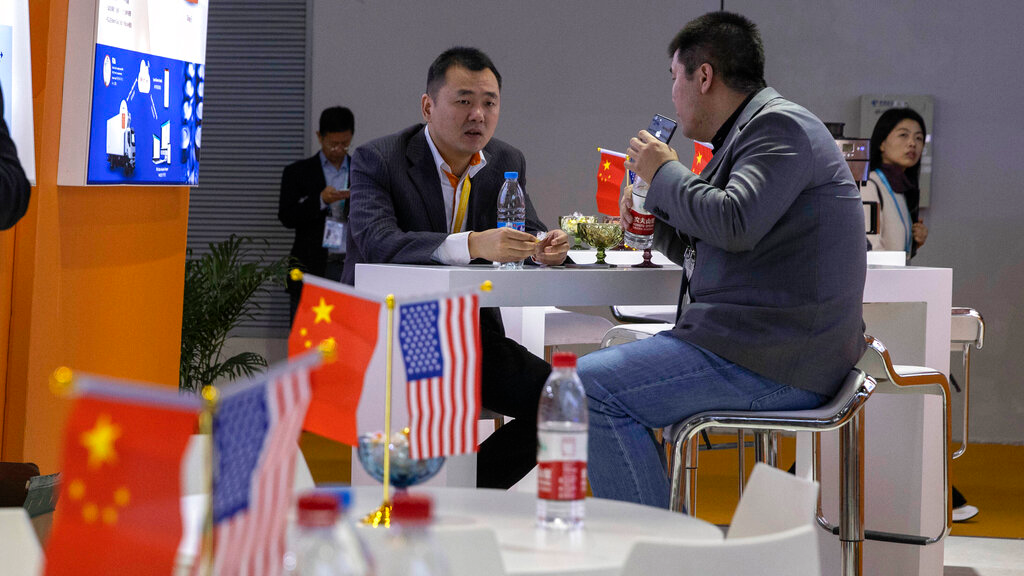 FILE - In this November 6, 2019, file photo, visitors chat near American and Chinese flags displayed at a booth for an American company promoting environmental sensors during the China International Import Expo in Shanghai. (AP Photo/Ng Han Guan, FIle)