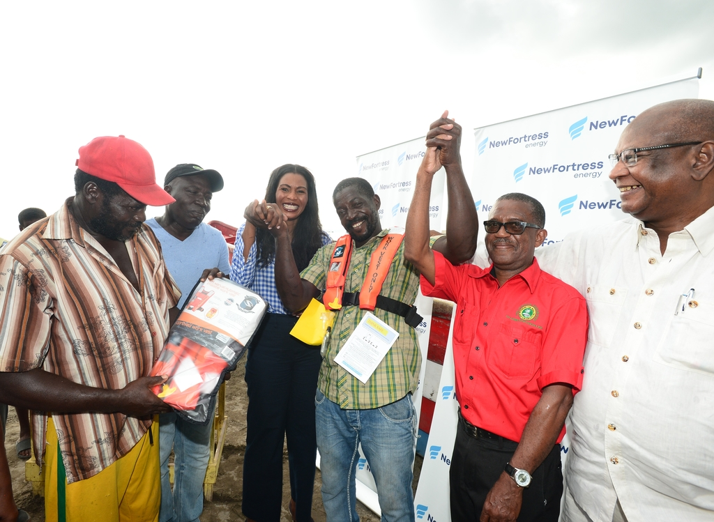 Cristen Blair, fisherman at the Old Harbour Bay Fishing Village examined his life jacket courtesy of New Fortress Energy. Sharing in the moment l-r: Christen Blair, Florizel Thompson, Verona Carter, VP, Public Affairs, New Fortress Energy, Leon Prince, Anthony Drysdale and Dr Conrad Douglas, Executive Chairman and Principal Consultant, Conrad Douglas & Associates (Environmental Science and Technology Ltd.)