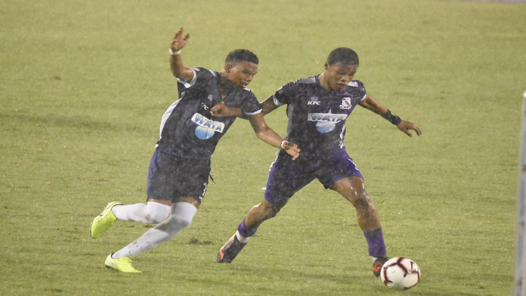 Photo shows action in the rain during second half play in the ISSA all-island Champions Cup semi-final game between Kingston College and Jamaica College at the National Stadium on Saturday, November 16, 2019. (PHOTOS: Marlon Reid).
