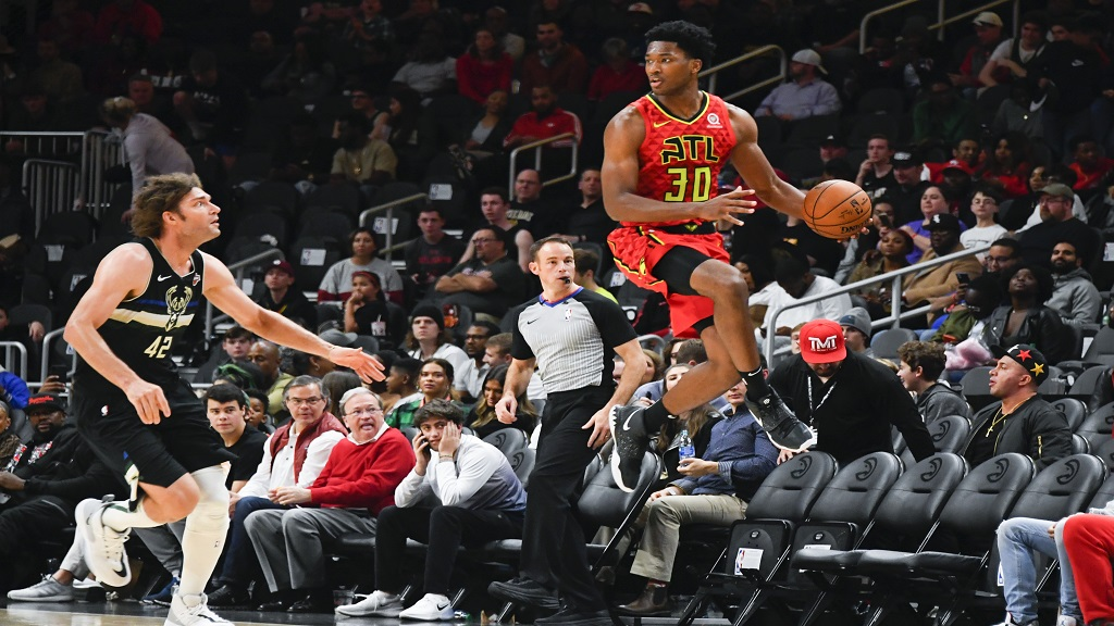 Atlanta Hawks center Damian Jones (30) saves a ball from going out of bounds as Milwaukee Bucks center Robin Lopez (42) defends during the second half of an NBA basketball game Friday, Dec. 27, 2019, in Atlanta. (AP Photo/John Amis).