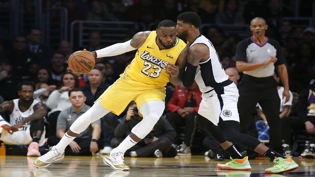 Los Angeles Lakers' LeBron James (23) is defended by Los Angeles Clippers' Paul George during the second half of an NBA basketball game Wednesday, Dec. 25, 2019, in Los Angeles. The Clippers won 111-106. (AP Photo/Ringo H.W. Chiu).