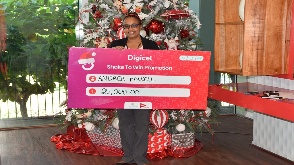"Andrea Howell displays the symbolic cheque given to her after she won $25,000 in the ""Digicel Shake to Win"" promotion."