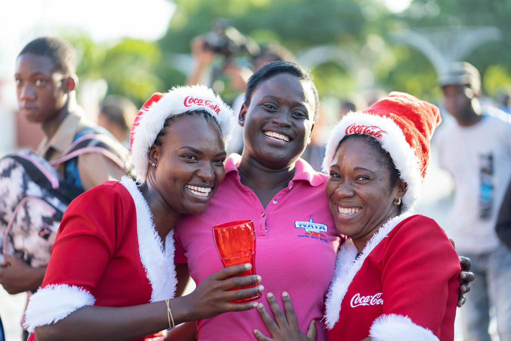 Coca Cola Brand Ambassadors dressed as Mrs. Clause added to the Christmas spirit while posing with Candice Bryan during the Coca-Cola Christmas Truck Tour stop at the William Grant Park in Downtown Kingston on Friday, November 22.