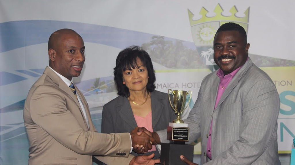 """Antony Bascoe (right), Bartender at The Courtleigh Hotel & Suites, receives the JHTA """"Employee of the Year Award"""" at the organization's 2017 Annual General Meeting and Awards Luncheon held recently in Kingston, Jamaica."""