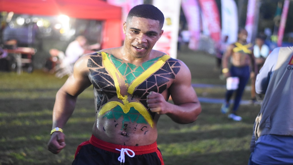 This runner, sporting a body  paint of the Jamaican colours, powers to the finish line at the Reggae Marathon on Sunday. (Photo: Marlon Reid)
