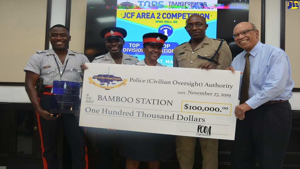 Executive Member of the Police (Civilian Oversight) Authority (PCOA), Marshall Hall (right), presents the 'Transforming Our Police Service' (TOPS) Competition first-place cheque to police staff of the Bamboo Police Station in St Ann at the awards ceremony at Couples San Souci in St Ann on November 27. The members are (from left) Constable Rohan Smith, Corporal Ronald Brown, Sergeant Patricia Brown; alongside Commander of the St. Ann Police Division, Senior Superintendent Calvin Small.