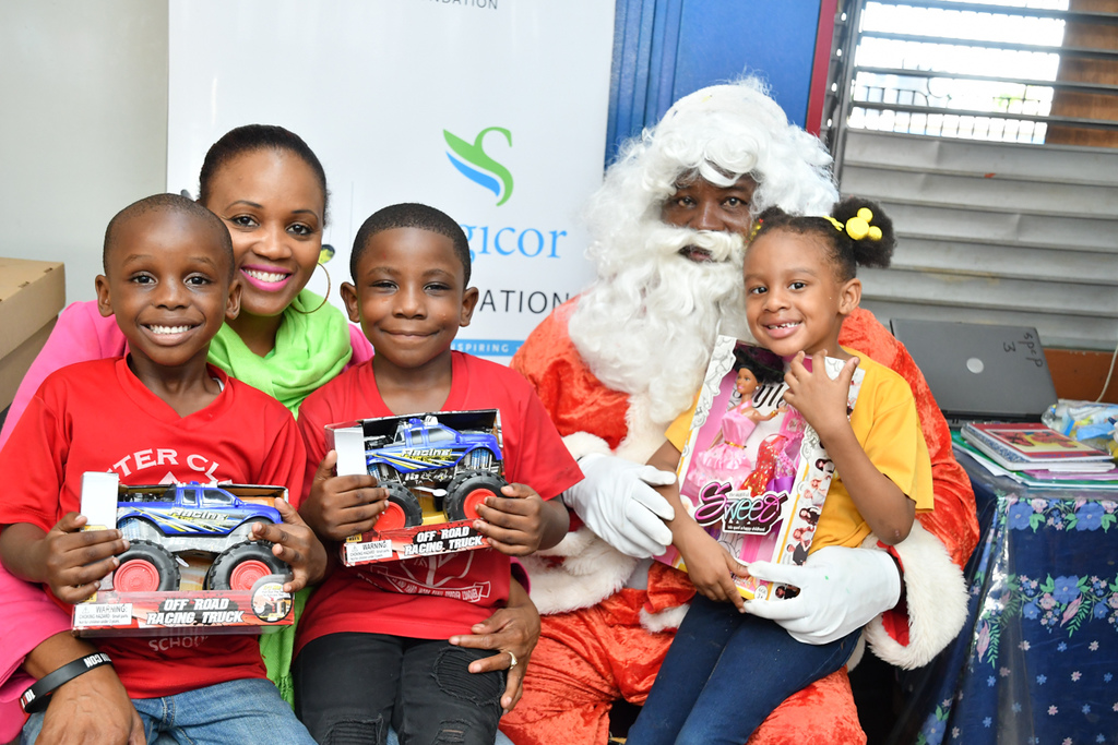 Wendy Wallace (2nd left), Sagicor Life Financial Advisor, plays the role of Santa's helper, gifting toy trucks and dolls to St. Peter Claver Infant School students (from left) Shaudon Matthews, Demetrie Nelson and Arihanna Blygen.