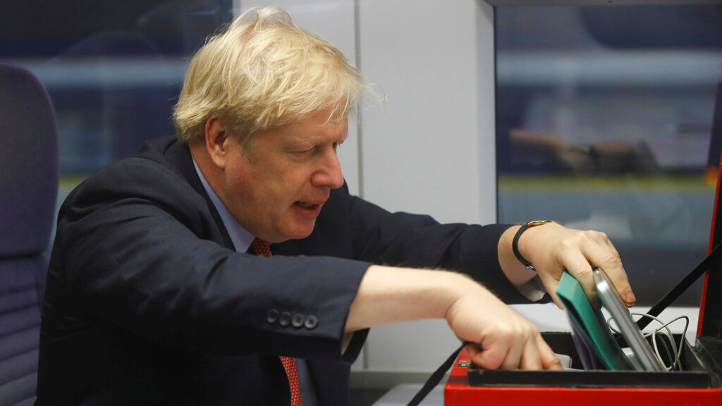 Britain's Prime Minister Boris Johnson sits on a train in London, December 6, 2019, on the campaign trail ahead of the general election on December 12. (Peter Nicholls/Pool via AP)