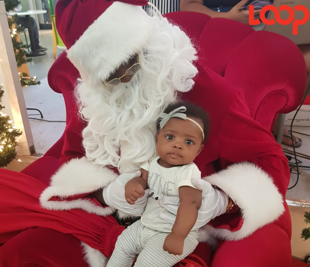 Baby Nuriah posing for a picture with Santa Claus.