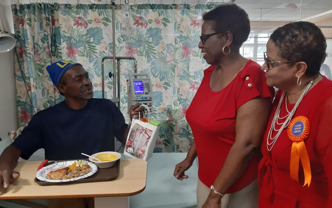 Patient, Stephen Arlington Gale receives his Christmas gift from members of the Cancer Support Services, Olga Lashley (left) and Jan Lynton (right).