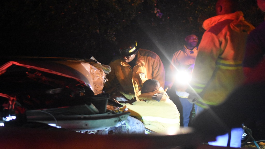Fire brigade personnel, in the company of police officers, engaged in the process of trying to free one of the passenger in a Toyota Axio motorcar which was involved in a crash along the Llandovery main road along the Northern Coastal Highway through St Ann on Saturday night, this after an armed robbery, murder and reported shootout between the occupants of the car and the police.  (Photos: Marlon Reid)