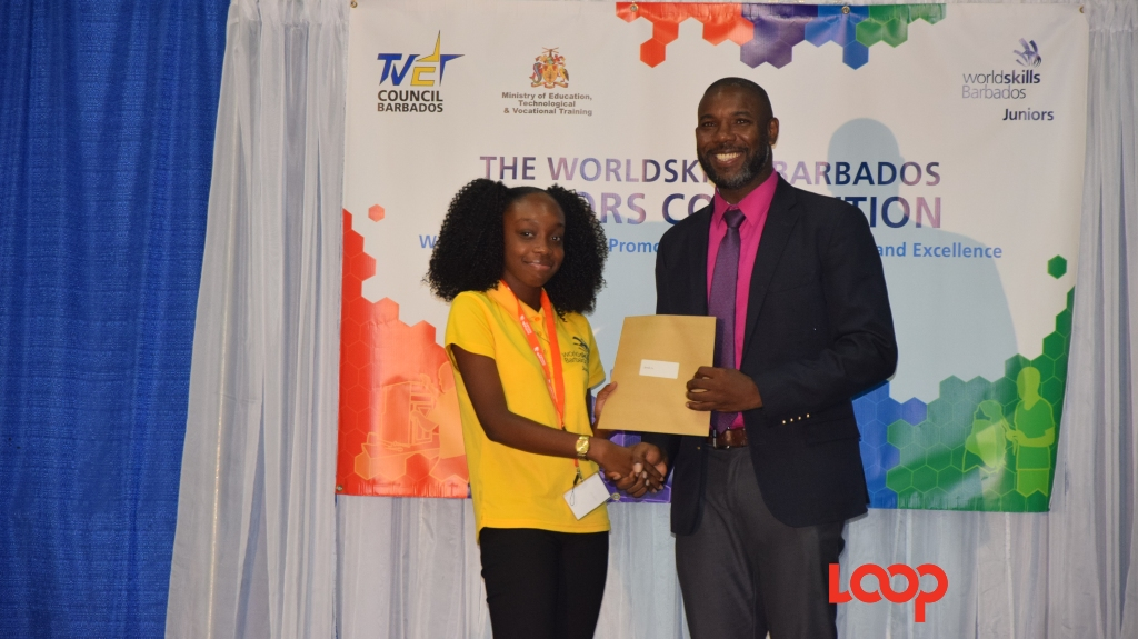 Korvele Cox accepts her certificate from permanent secretary in the Ministry of Education, Technological and Vocational Training, Dr Romel Springer