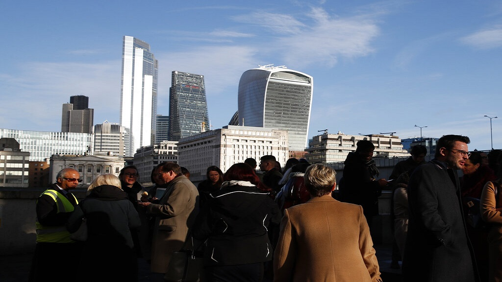 In this file photo dated Wednesday, Dec. 11, 2019, people gather near London Bridge, backdropped by the city of London financial district, with 20 Fenchurch Street building known as The Walkie-Talkie building, top right.  (AP Photo)