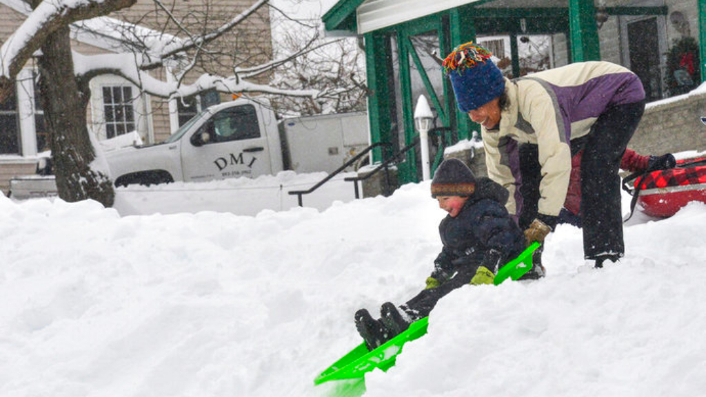 Child and parent sledding in snow (Source: Kristopher Radder ASSOCIATED PRESS)