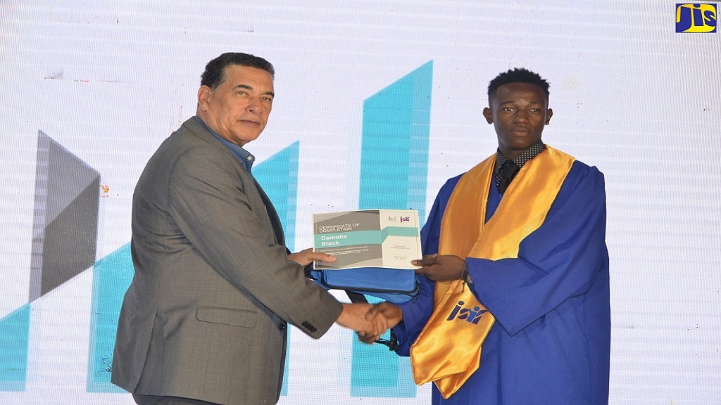 Mayor of Montego Bay Homer Davis presents a Certificate of Completion to Damalla Black at the western Event Production Training Programme graduation ceremony, held on Monday in Montego Bay.