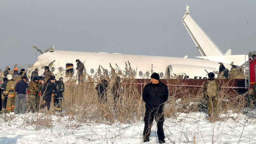 Police guard as rescuers work on the side of a plane crashed near Almaty International Airport, outside Almaty, Kazakhstan, Friday, Dec. 27, 2019. (AP Photo/Vladimir Tretyakov)