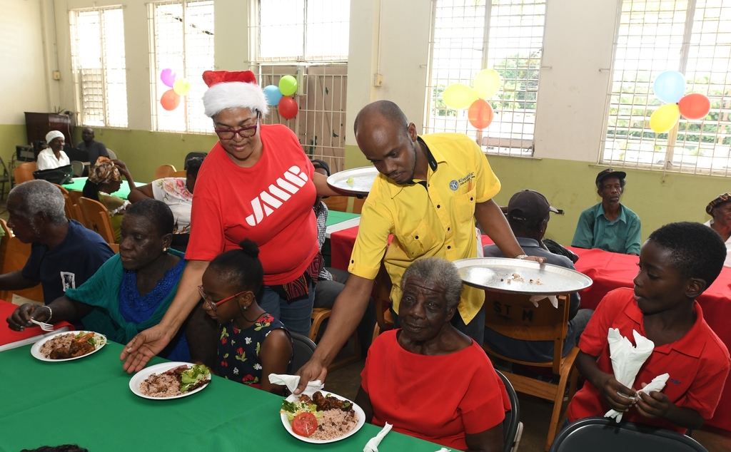 JMMB's Jennifer Williams (standing, left) and Kenrick Reid (right, standing), chairman, community service and special projects, Kiwanis Club of Liguanea are pleased to play host to senior citizens from the Liguanea communities including: Standpipe, Mona Common and Papine, at the club's annual Christmas treat, which this year saw JMMB coming on board.