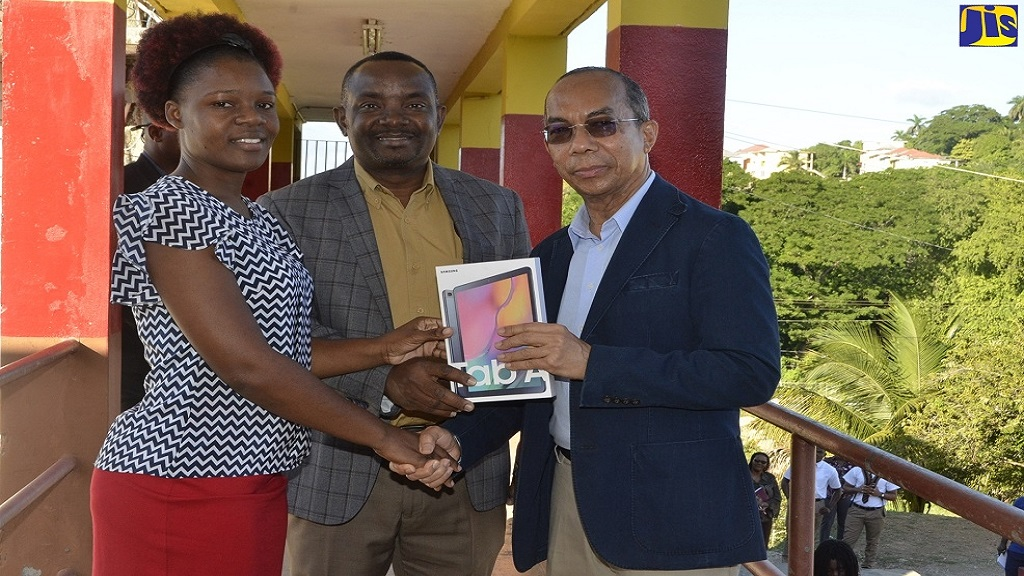 Minister of National Security, Hon. Dr. Horace Chang (right) presents a tablet computer to Principal of Cornwall College, Michael Ellis (centre) and Acting Head of the Information Technology and Business Department at the school, Audia Cole on the grounds of the institution in Montego Bay, St James. (Photo: Nickieta Sterling, JIS)