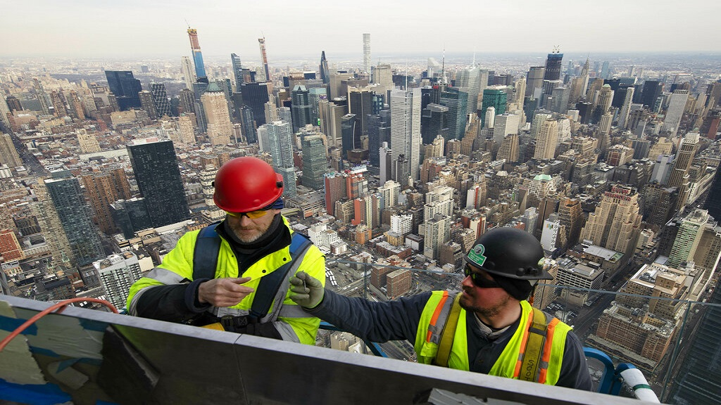 In this March 8, 2019, file photo, work continues on an outdoor observation deck on the 30 Hudson Yards office building in New York. Business economists expect U.S. economic growth to slow this year and next, but they say the economy will avoid recession. (AP Photo/Mark Lennihan, File).