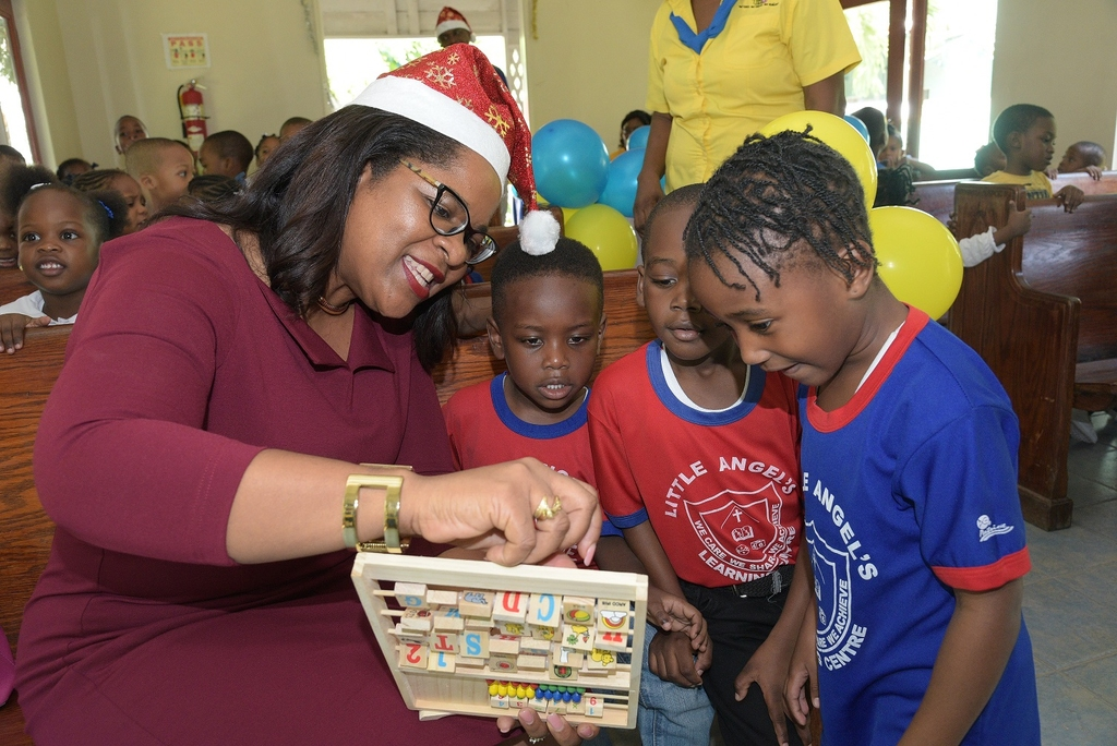 General Manager of IGT Jamaica, Debbie Green shows some students of the Little Angels Learning Centre how to work a learning toy during a recently held Christmas Treat at Mustard Seed Communities Sophie's Place in Gordon Town put on by IGT Jamaica at which the children were treated to educational toys.