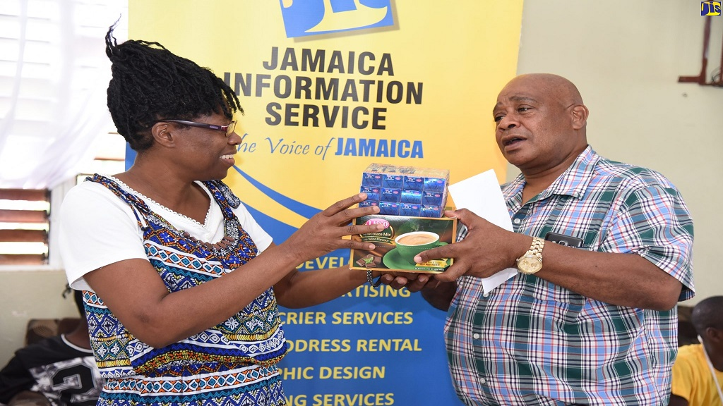 Director of the Mt Olivet Boys' Home in Manchester, Patrick Newman, accepts items from a member of the Jamaica Information Service (JIS) team, Marcia Carr, during the agency's visit ahead of Christmas. The JIS is celebrating 10 years since its adoption of the home.