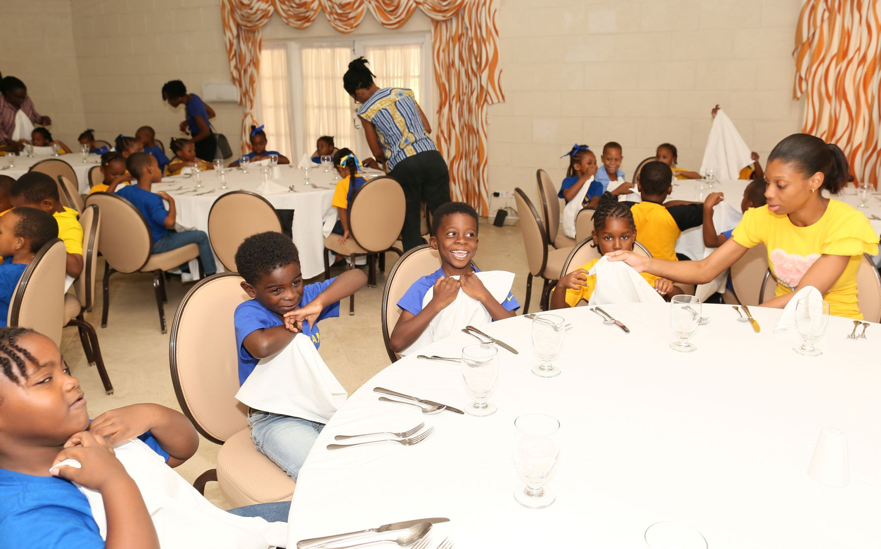 Tamarind Hotel's Operations Manager Antonia Hinds assisting some of the West Terrace Primary School students during their recent lunch and an etiquette session hosted by the St. James property.