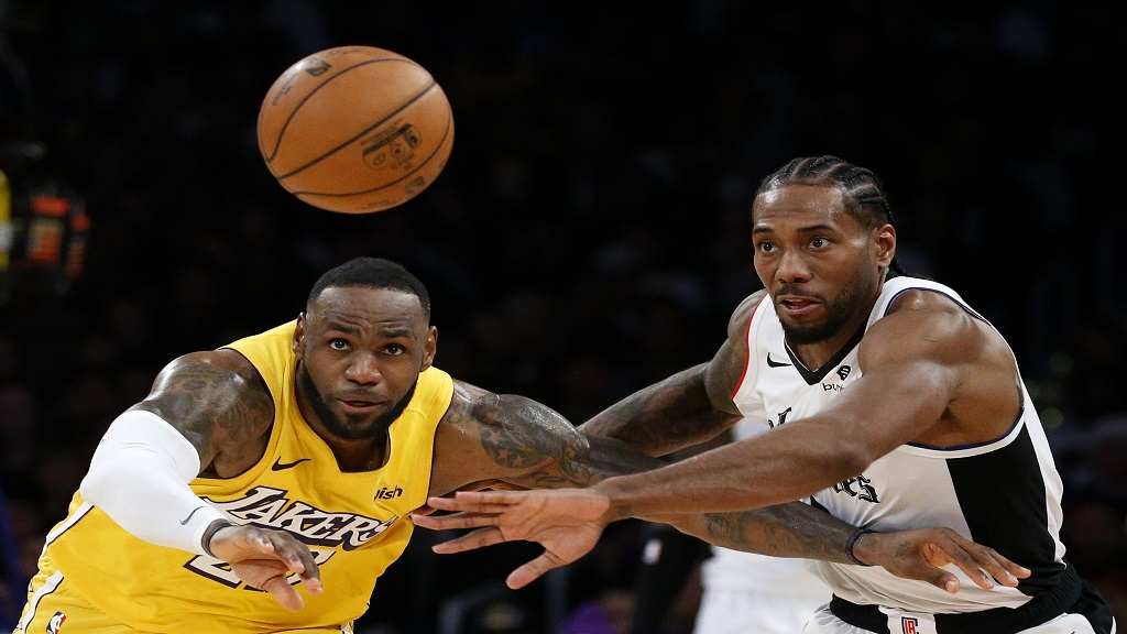 Los Angeles Lakers' LeBron James, left, and Los Angeles Clippers' Kawhi Leonard (2) chase the ball during the second half of an NBA basketball game Wednesday, Dec. 25, 2019, in Los Angeles. The Clippers won 111-106. (AP Photo/Ringo H.W. Chiu).